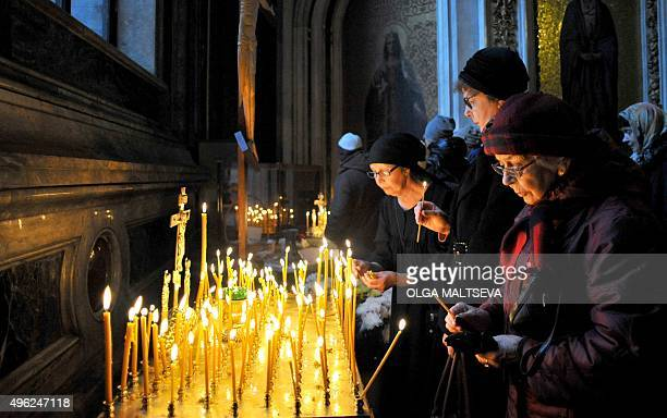 Orthodox believers light on November 8 2015 candles for the victims of the Russian MetroJet Airbus A321 crash during a service in St Isaac's...