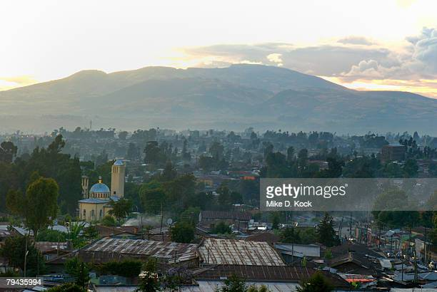 Orthodox christian churches and mosques dot the landscape of Addis Ababa whilst smoke from cooking fires lingers in the air. Ethiopia, Africa