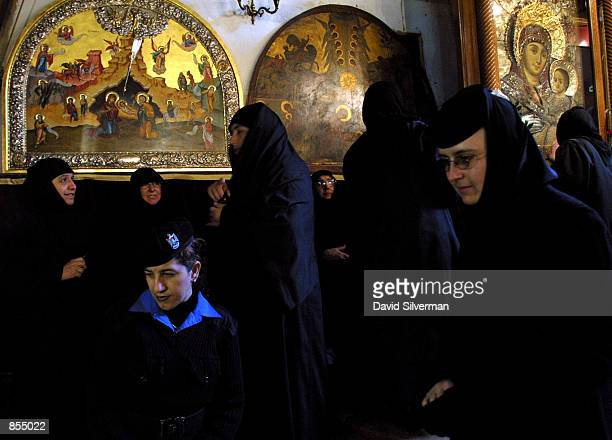 Orthodox Christian nuns and a Palestinian policewoman gather under holy icons January 6 2002 during Orthodox Christmas Eve in the Church of the...
