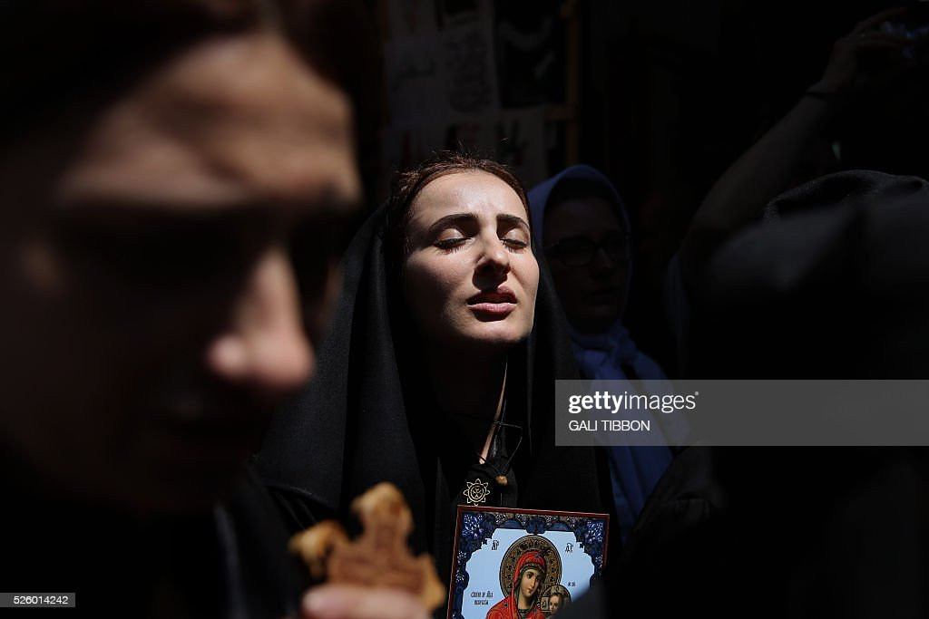 Orthodox Christian pilgrims from Abkhazia walk along the Via Dolorosa (Way of Suffering), during the Good Friday procession in Jerusalem's old city on April 29, 2016. Thousands of pilgrims took part in processions along the route where, according to tradition, Jesus carried the cross during his last days. / AFP / GALI
