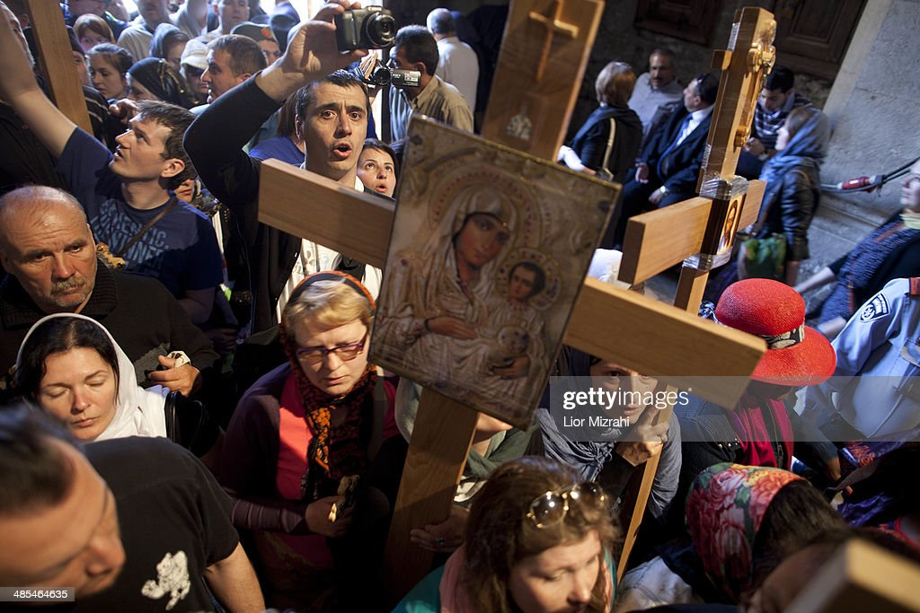 Orthodox Christian pilgrims hold wooden crosses as they arrive to the Church of the Holy Sepulchre on April 18 2014 in Jerusalem's old city...