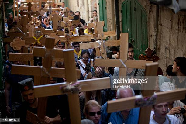 Orthodox Christian pilgrims hold wooden crosses as they take part in the Good Friday procession along the Via Dolorosa on April 18 2014 in...