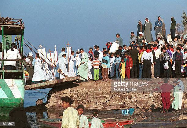 Orthodox Christian preists and bishops disembark after sailing across to the east bank of the Nile on a sailboat only used during celebrations...