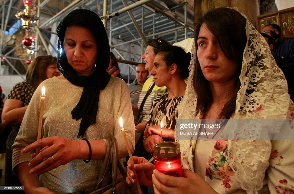 Orthodox Christian worshippers take part in the 'Holy Fire' ceremony at the Church of the Nativity in the West Bank town of Bethlehem on April 30, 2016, during the Orthodox Easter. The ceremony is marked by the appearance of 'sacred fire' in the two cavities on either side of the Holy Sepulchre, in the Church of the Sepulchre in Jerusalem, and Christians all over the world light candles representing this 'Holy Fire'. The Holy Sepulchre in Jerusalem is the site of the tomb of Jesus Christ according to Christian tradition. / AFP / MUSA