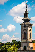 Orthodox church tower with clock under blue sky with clouds and flying bird, Belgrade