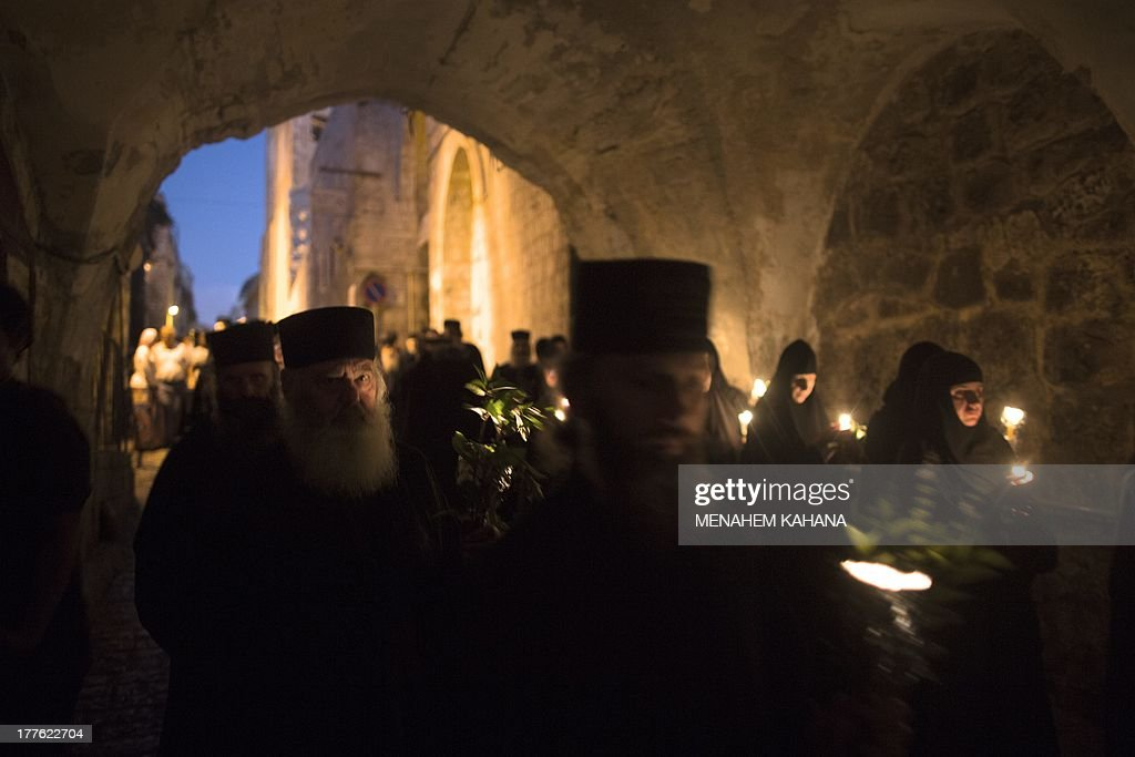 Orthodox clergymen and nuns holding candles and flowers walk on August 25, 2013 along the narrow streets of Jerusalem's Old City in a religious procession marking The Dormition of the Theotokos (God-bearer) which commemorates the Virgin Mary. Thousands of Christian Orthodox clergy and pilgrims took part in the early morning procession, an annual event during which Orthodox believers carry an icon of the Virgin Mary from the Church of the Holy Sepulchre to Mary's Tomb Church, located on the foothills of the Mount of Olives, near Gethsemane garden, which is regarded as the burial place of Virgin, according to Christian tradition.