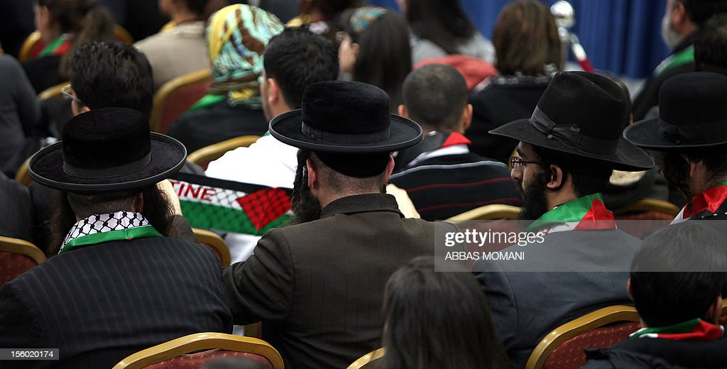 Orthodox Jews, wearing Palestinian flag scraves around their necks, listens to Palestinian President Mahmud Abbas delivering a speech to mark the eighth anniversary of the death of the late leader Yasser Arafat, in the West Bank city of Ramallah on November 11, 2012. Palestinians are coordinating with Russia, as well as Swiss and French experts, on the exhumation of Arafat who died in a French military hospital near Paris on November 11, 2004, and who French experts were unable to say what had killed him. Many Palestinians are convinced he was poisoned. AFP PHOTO/ABBAS MOMANI