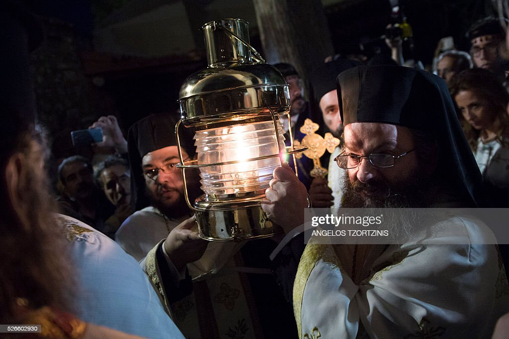 Orthodox priests carry the 'Holy Fire' as worshippers gather during the Orthodox Easter ceremony at the Church of Metochi Panagiou Tafou in Athens, on April 30, 2015. Millions of Greeks flock to churches around the country this week to celebrate Easter, the country's foremost religious celebration. / AFP / ANGELOS