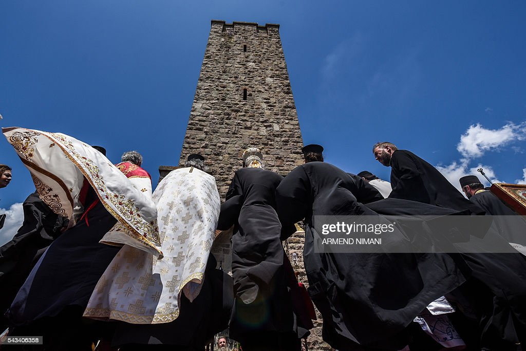 Orthodox priests congregate at the Gazimestan memorial, near the village of Mazgit, Kosovo, as people take part in a ceremony marking the historic 'Battle of Kosovo' on June 28, 2016. The ceremony marks the Battle of Kosovo in 1389 when the Serbian army was defeated by the Ottoman Empire. / AFP / ARMEND