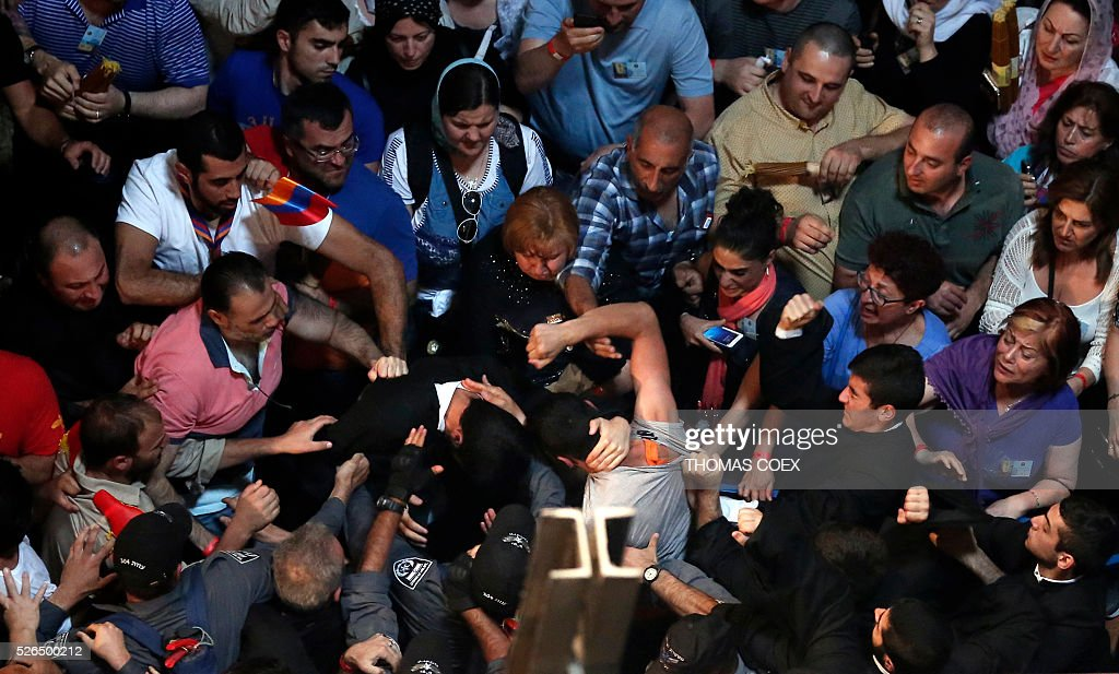Orthodox priests, pilgrims and Israeli policemen scuffle before the ceremony as thousands gather in the Church of the Holy Sepulchre in Jerusalem's Old City, on April 30, 2016, during the Orthodox Easter ceremony of the 'Holy Fire'. The ceremony celebrated in the same way for eleven centuries, is marked by the appearance of 'sacred fire' in the two cavities on either side of the Holy Sepulchre. / AFP / THOMAS