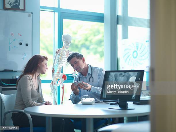 Orthopaedic consultant with patient in consulting room
