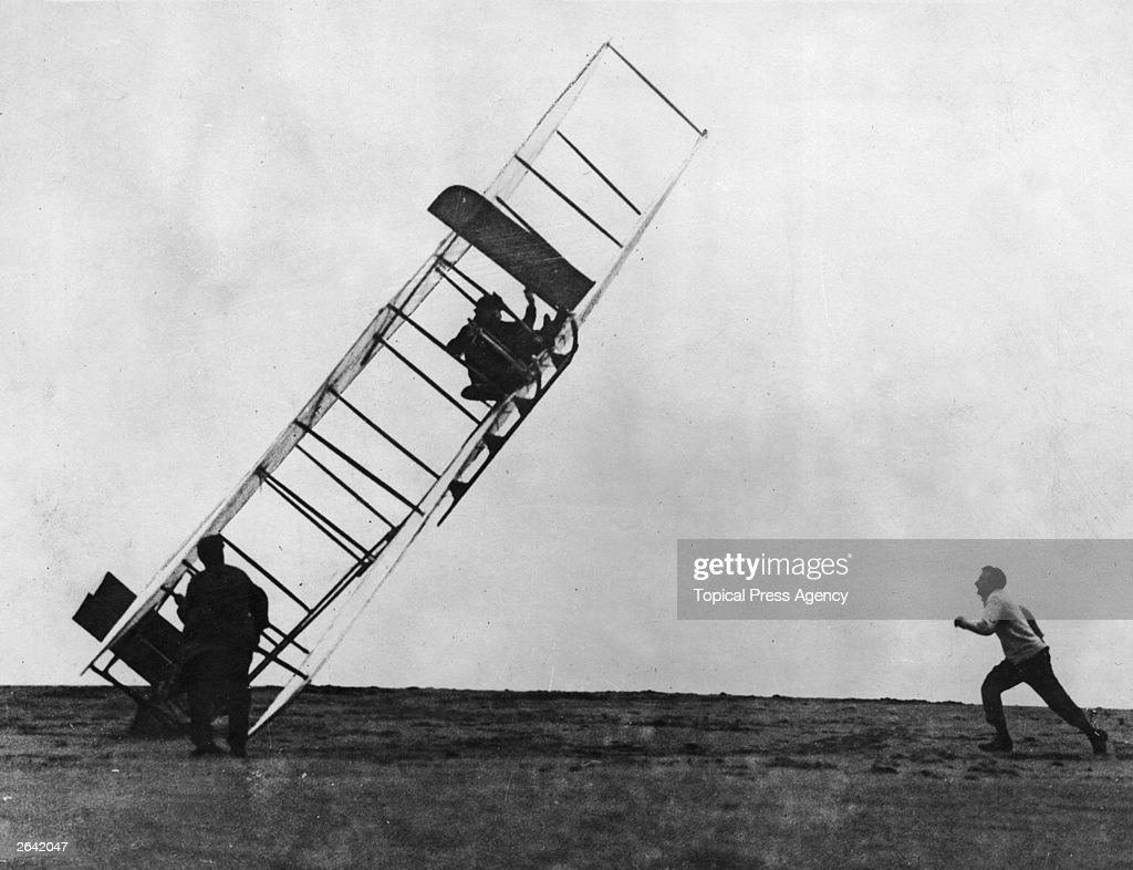 Orville Wright (1871 - 1948) lands one of the early Wright gliders badly, overseen by his brother Wilbur (1867 - 1912).