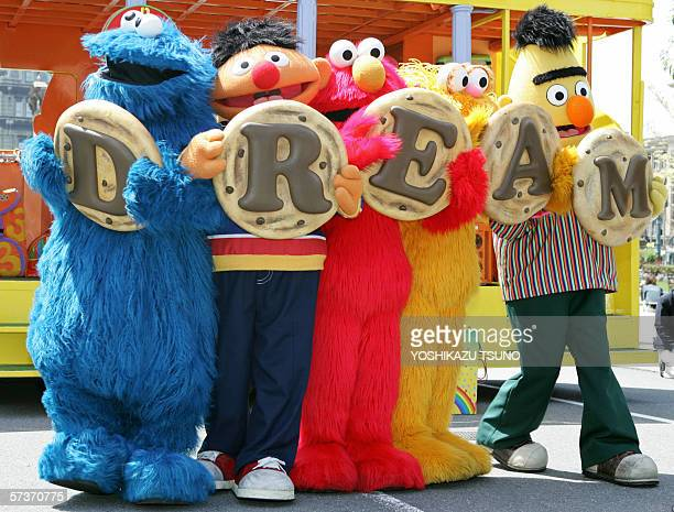 Sesame Street character Cookei Monster Earnie Elmo Zoe and Bert shows large cookies with letters to spell dream to celebrate the fifth anniversary of...