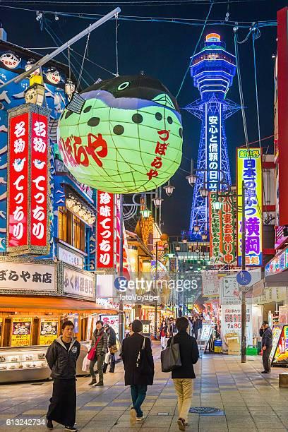 Osaka neon night Tsutenkaku Tower overlooking people in Shinsekai Japan
