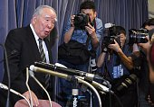Osamu Suzuki chairman of Japan's automaker Suzuki gestures to photographers at the end of a press conference after reporting to the transport...
