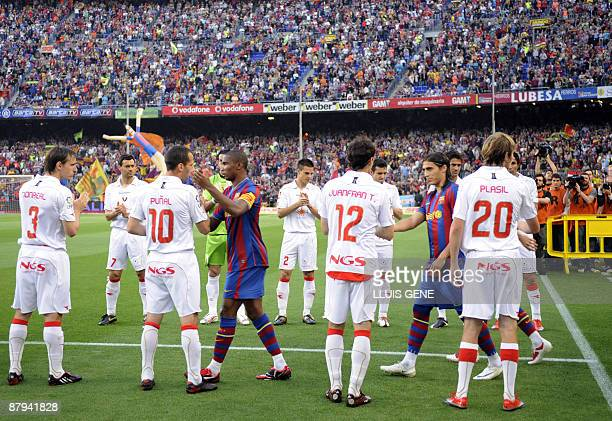 Osasuna players shake hands with Barcelona players as the new Spanish league football Champions at at the New Camp Stadium in Barcelona on May 23...