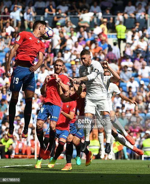 Osasuna's forward Kenan Kodro jumps for the ball past Real Madrid's defender Sergio Ramos during the Spanish league football match Real Madrid CF vs...