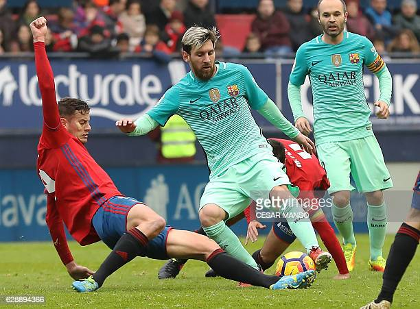 Osasuna's forward Oriol Riera vies with Barcelona's Argentinian forward Lionel Messi during the Spanish league football match CA Osasuna vs FC...