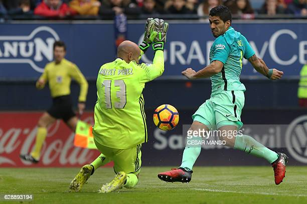 Osasuna's goalkeeper Nauzet Perez vies with Barcelona's Uruguayan forward Luis Suarez during the Spanish league football match CA Osasuna vs FC...
