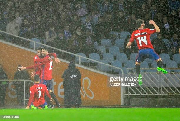 Osasuna's players celebrate after scoring their team's first goal during the Spanish league football match Real Sociedad vs CA Osasuna at the Anoeta...