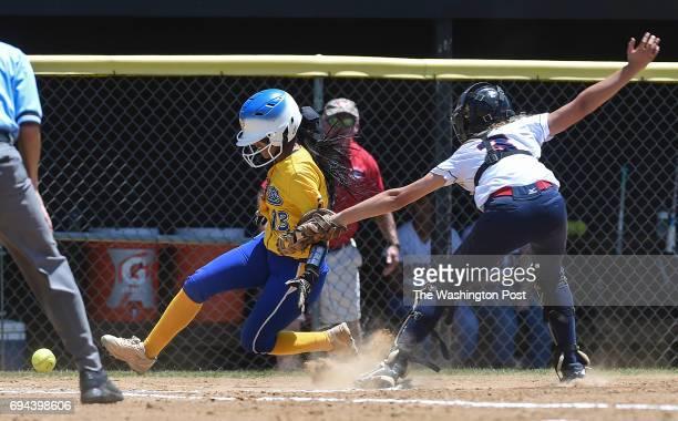 Osborn Park's Yari Santos scores as Grassfield catcher Savannah Etheridge loses the ball during the Virginia 6A State Softball Semifinal game between...