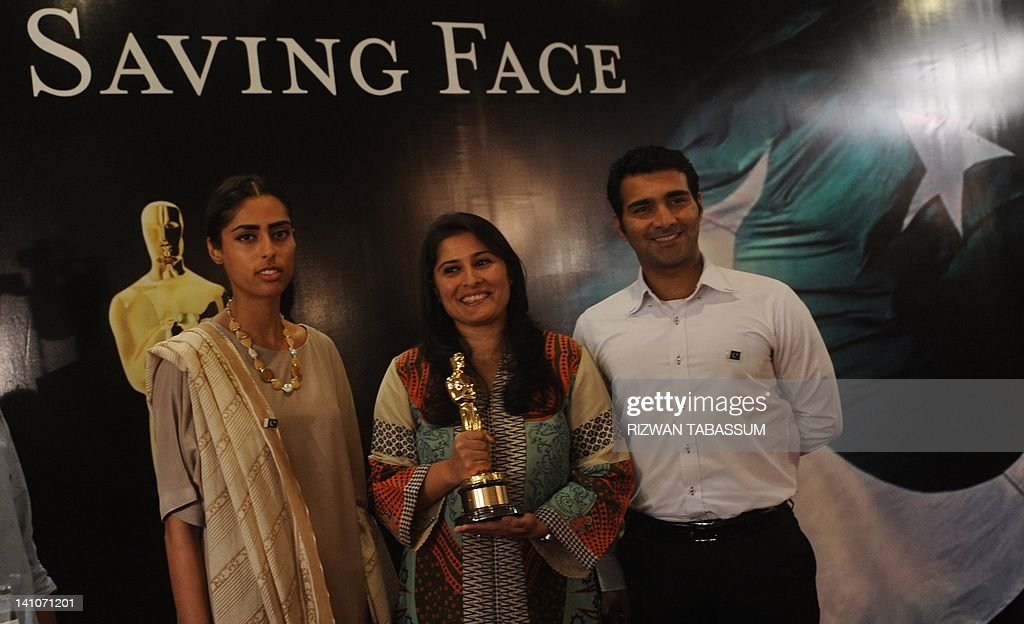 Oscar award winning Pakistani director Sharmeen Obaid-Chinoy (C) shows her Oscar award as she poses with cameraman Asad Faruqi (R) and producer Fazeelat Aslam (L) during a press conference in Karachi on March 10, 2012. Pakistan's first Oscar winner launched a campaign, hoping that her documentary about survivors of acid attacks can help eliminate a crime that disfigures hundreds of women each year. AFP PHOTO/Rizwan TABASSUM