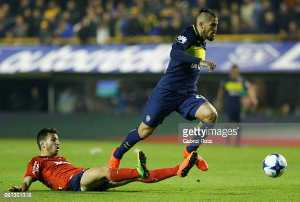 Oscar Benitez of Boca Juniors fights for the ball with Juan Sanchez Mino of Independiente during a match between Boca Juniors and Independiente as...