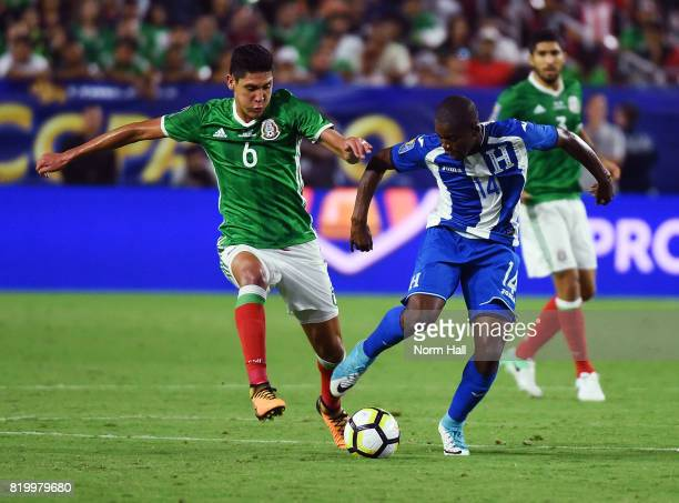 Oscar Boniek Garcia of Honduras brings the ball up field while being defended by Bryan Acosta of Mexico during the second half in a quarterfinal...