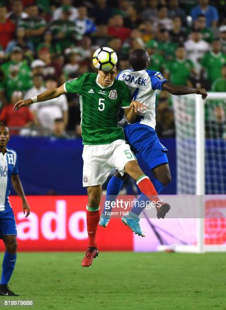 Oscar Boniek Garcia of Honduras challenges Jesus Molina of Mexico for a head ball during the second half in a quarterfinal match during the CONCACAF...