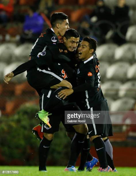 Oscar Cardozo of Libertad celebrates with teammates Angel Cardozo Lucena and Antonio Bareiro after scoring the opening goal of his team during a...