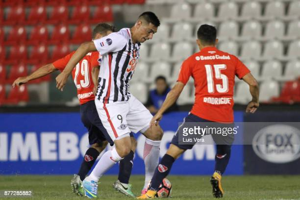 Oscar Cardozo of Libertad fights for the ball with Diego Rodriguez and Nicolas Domingo of Independiente during a first leg match between Libertad and...