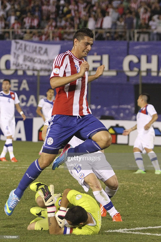 Oscar Cardozo (L) of Paraguay and Claudio Vargas (R) of Chile fights for the ball during the match between Paraguay and Chile as part of the South American Qualifiers for FIFA World Cup Brazil 2014, at Defensores del Chaco Stadium on June 07, 2013 in Asuncion, Paraguay.