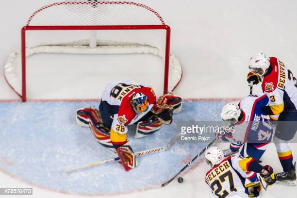 Oscar Dansk of the Erie Otters defends the net against Ryan Moore of the Windsor Spitfires on March 13 2014 at the WFCU Centre in Windsor Ontario...