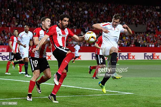 Oscar de Marcos and Raul Garcia of Athletic Club Bilbao challenge for the ball with Grzegorz Krychowiak of Sevilla during the UEFA Europa League...