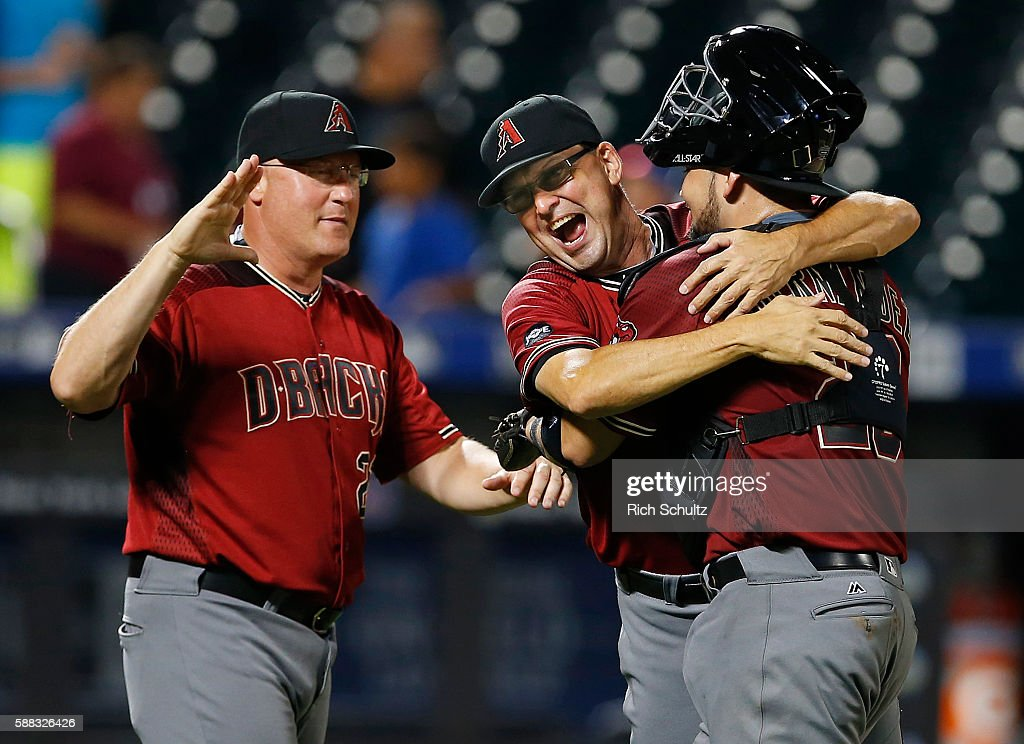 Oscar Hernandez #28 of the Arizona Diamondbacks is hugged by assistant hitting coach Mark Grace #17 and congratulated by pitching coach Mike Butcher #23 after the Diamondbacks defeated the New York Mets 3-2 in 12 innings during a game at Citi Field on August 10, 2016 in the Flushing neighborhood of the Queens borough of New York City. The Diamondbacks won 3-2.