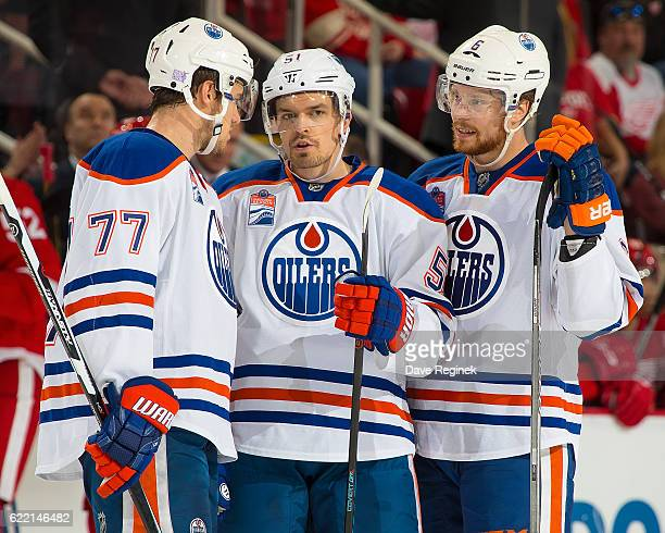 Oscar Klefbom Anton Lander and Adam Larsson of the Edmonton Oilers chat on a play stoppage during an NHL game against the Detroit Red Wings at Joe...