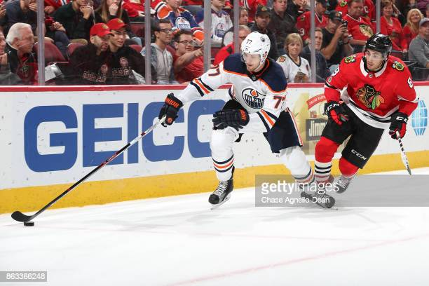Oscar Klefbom of the Edmonton Oilers grabs the puck ahead of Nick Schmaltz of the Chicago Blackhawks in overtime at the United Center on October 19...