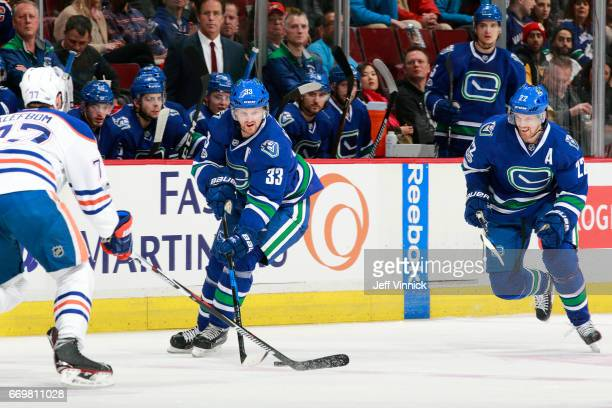Oscar Klefbom of the Edmonton Oilers looks on as Henrik Sedin and Daniel Sedin of the Vancouver Canucks skate up ice during their NHL game at Rogers...