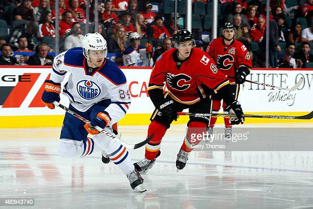 Oscar Klefbom of the Edmonton Oilers skates against Joe Colborne of the Calgary Flames at Scotiabank Saddledome on December 31 2014 in Calgary...