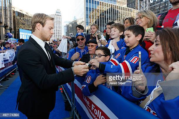 Oscar Lindberg of the New York Rangers signs autographs for fans as he walks down the Blue Carpet prior to the game against the Columbus Blue Jackets...