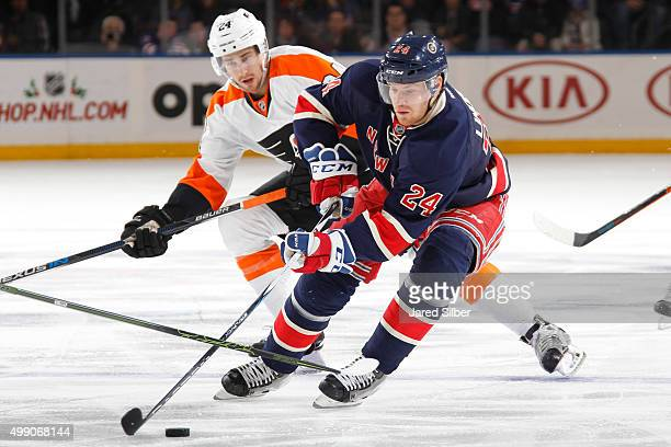 Oscar Lindberg of the New York Rangers skates with the puck against Matt Read of the Philadelphia Flyers at Madison Square Garden on November 28 2015...