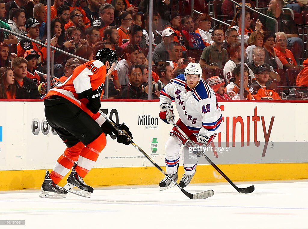 Oscar Lindberg of the New York Rangers takes the puck as Samuel Morin of the Philadelphia Flyers defends on September 30 2014 at the Wells Fargo...