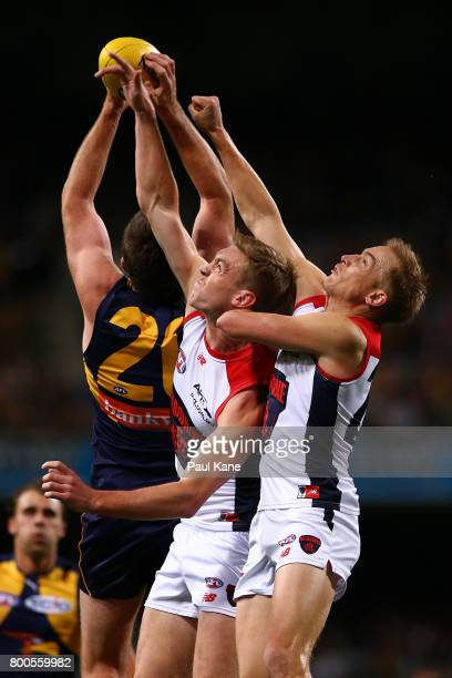 Oscar McDonald and Bernie Vince of the Demons attempt to spoil the mark for Jeremy McGovern of the Eagles during the round 14 AFL match between the...