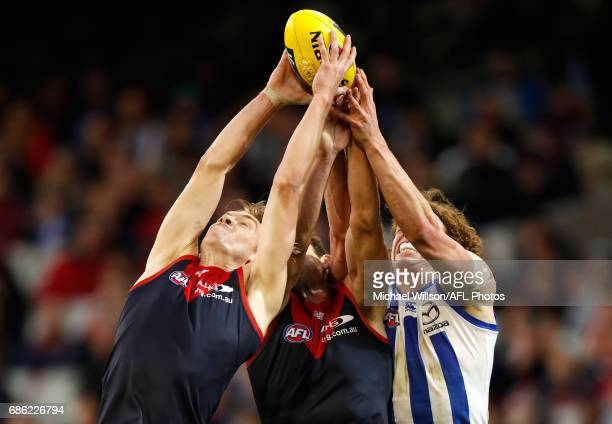 Oscar McDonald and Cameron Pedersen of the Demons compete for the ball against Ben Brown of the Kangaroos during the 2017 AFL round 09 match between...