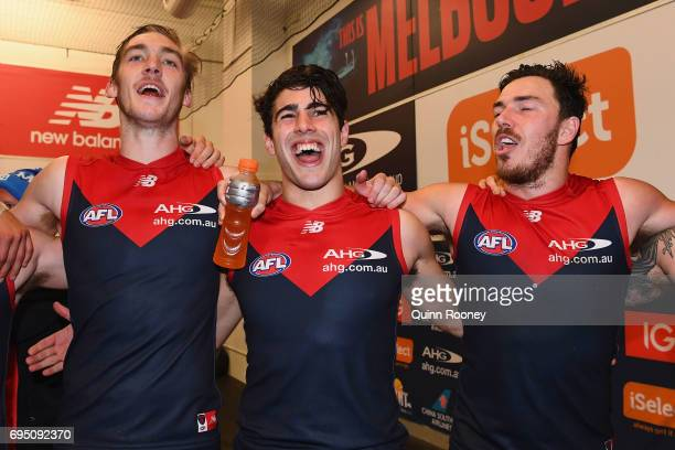 Oscar McDonald Christian Petracca and Michael Hibberd of the Demons sing the song in the rooms after winning the round 12 AFL match between the...