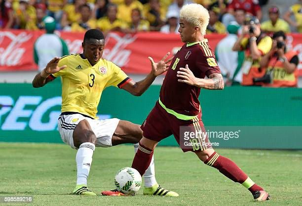 Oscar Muilllo of Colombia struggles for the ball with Adalberto Peñaranda of Venezuela during a match between Colombia and Venezuela as part of FIFA...