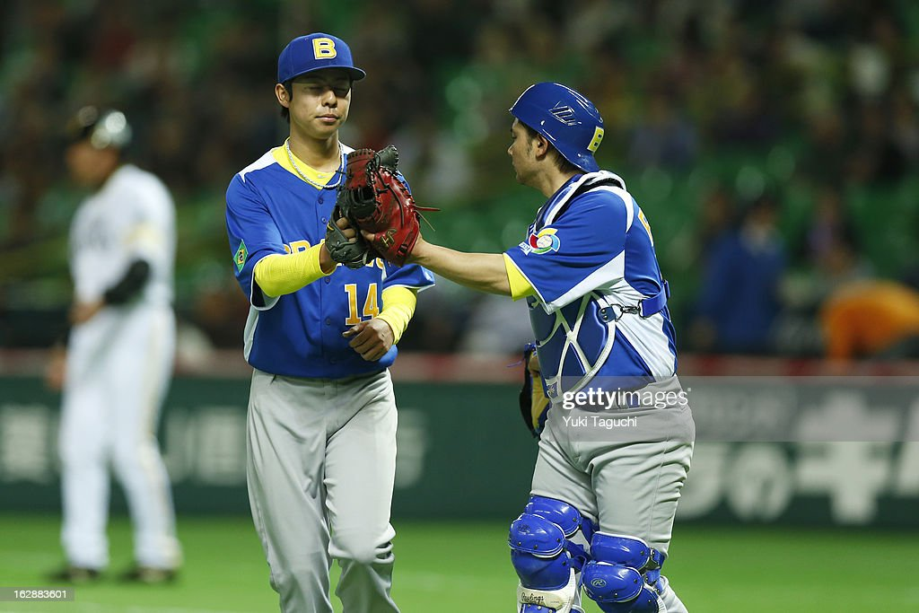 Oscar Nakaoshi #14 of Team Brazil is greeted by Diego Franca #12 of Team Brazil as they head back to the dugout during the World Baseball Classic exhibition game against the SoftBank Hawks at the Fukuoka Yahoo! Japan Dome on Thursday, February 28, 2013 in Fukuoka, Japan.