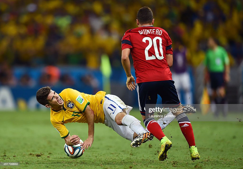 Oscar of Brazil falls after a challenge by Juan Fernando Quintero of Colombia during the 2014 FIFA World Cup Brazil Quarter Final match between...