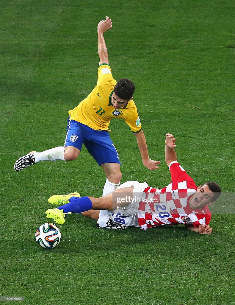 Oscar of Brazil is challenged by Mateo Kovacic of Croatia during the 2014 FIFA World Cup Brazil Group A match between Brazil and Croatia at Arena de Sao Paulo on June 12, 2014 in Sao Paulo, Brazil.