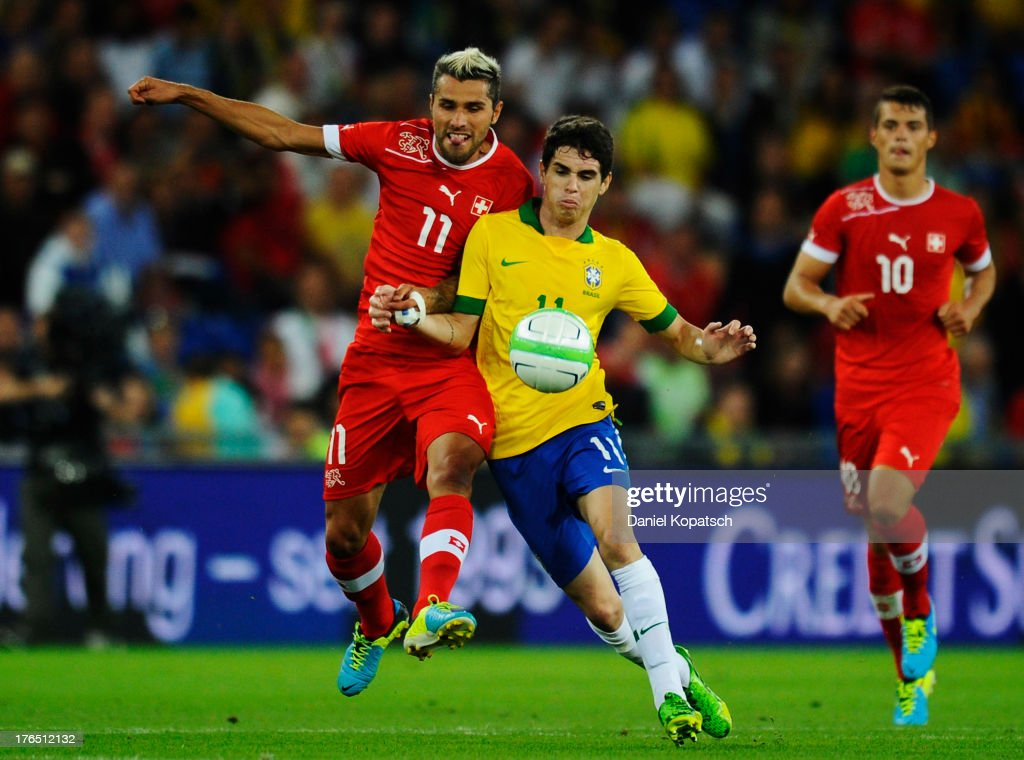 Oscar of Brazil (R) is challenged by <a gi-track='captionPersonalityLinkClicked' href=/galleries/search?phrase=Valon+Behrami&family=editorial&specificpeople=453450 ng-click='$event.stopPropagation()'>Valon Behrami</a> of Switzerland during the international friendly match between Switzerland and Brazil at St. Jakob Stadium on August 14, 2013 in Basel, Switzerland.